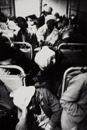 3:30 a.m. Going to work: The interior of this bus is dimly lit by a small green bulb at one end of the aisle and a small red one at the other. But once it reaches the highway, the headlights of the stream of buses and taxis taking workers to Pretoria are an almost continuous glare through the rear window.