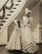 Little Girl and Woman in Formal Gowns, Looking up Staircase